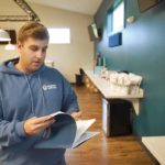 Employee browsing educational literature at Temescal Wellness Pittsfield marijuana dispensary
