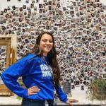 Employee with Photo Wall at Theory's Chicopee Dispensary - Credit Theory